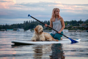 woman and dog on paddle board